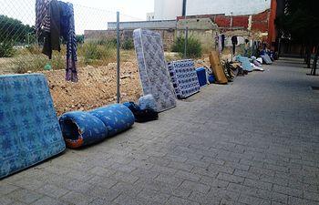 Bayod mira hacia a otro lado, mientras que personas sin hogar pernoctan en la calle, a las puertas del Albergue municipal