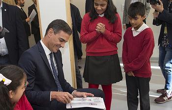 """El presidente del Gobierno, Pedro Sánchez, junto con los niños del Centro de Intervención y Recursos para la Infancia y la Adolescencia de Vallecas, gestionado por """"Save the Children""""."""