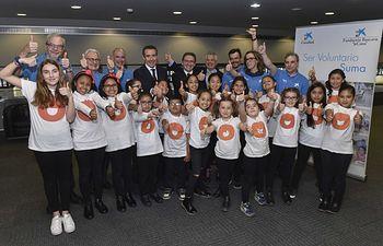 """El director general de la Fundación Bancaria """"la Caixa"""", Jaume Giró, y el director general de CaixaBank, Juan Alcaraz, en el centro de la imagen, rodeados por representantes de las delegaciones de voluntarios de """"la Caixa"""" y niños beneficiarios de la entidad social Vozes, en el acto central de homenaje a los voluntarios, en Barcelona."""