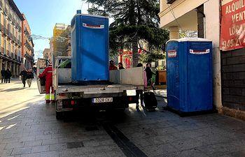 Operarios descargan WC químico para vermus navideños.