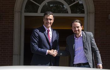 El presidente del Gobierno, Pedro Sánchez, saluda al secretario general de Podemos, Pablo Iglesias, a su llegada a La Moncloa.
