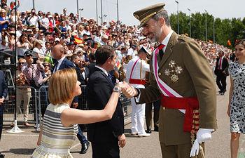 Su Majestad el Rey recibe el saludo de la ministra de Defensa, María Dolores de Cospedal, a su llegada al acto