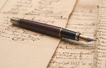 Imagen de una pluma sobre papel escrito