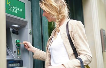Woman in city center withdrawing money from ATM machine. Foto: ©goodluz - stock.adobe.com