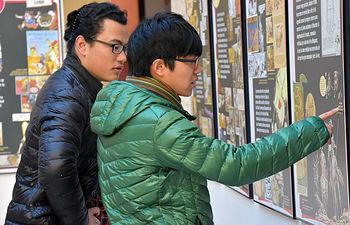 Dos estudiantes internacionales contemplan la muestra en el vestíbulo de Humanidades.