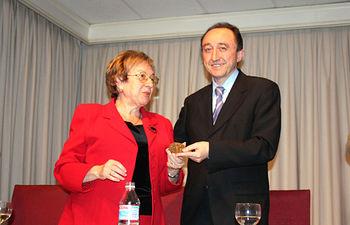 La presidenta de la Federación de Comunidades Originarias de Castilla-La Mancha en Madrid, Olga Alberca, entrega la medalla de esa entidad al consejero de Salud y Bienestar Social, Fernando Lamata.