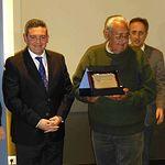 El alcalde de Campo de Criptana, Santiago Lúcas Torres, entrega el reconocimiento al 'cura de la caza' Buenaventura Soriano