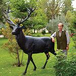 """Samuel Flores, en el jardín de su casa, junto a una réplica de uno de los récord de España cobrados en la finca """"El Palomar""""."""